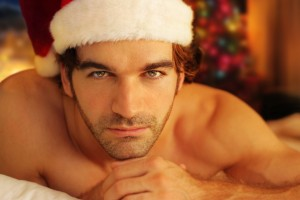 Young man bathed in warm light from fireplace wearing Santa cap